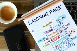 sheet of paper that says landing page with illustration next to coffee cup