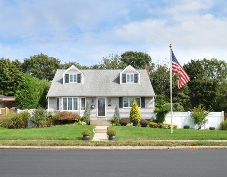 cape cod house with flag in front lawn