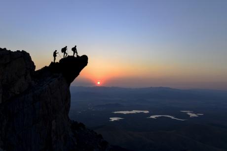 people climbing mountain at sunrise