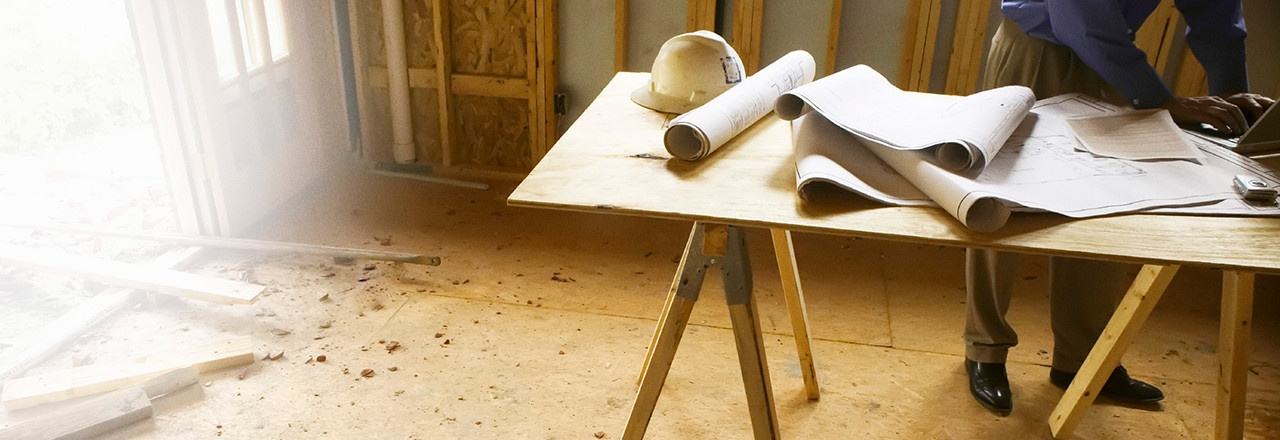 Home Builder Working on laptop with blueprints on a table