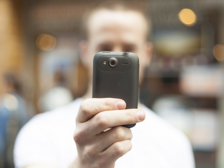 man holding smartphone camera in front of face