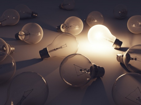 one lit lightbulb amongst unlit bulbs