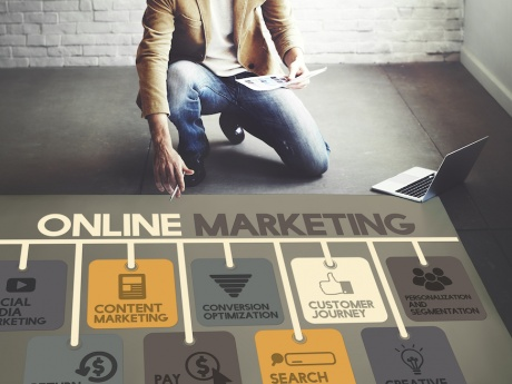 man laying out plan on floor with words online marketing painted on it