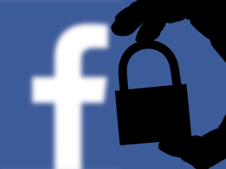 Facebook Logo with the Shadow of a Hand Holding a Lock