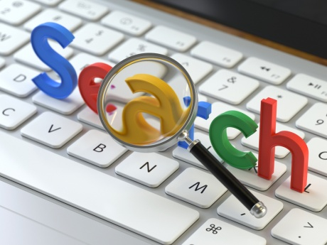 colorful letters spelling out SEARCH laid out on keyboard with magnifying glass