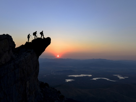 people climbing mountain at sunrise